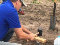 man hammering in a bulk density ring on a farm