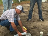 A man testing soil in a field with water in a beaker